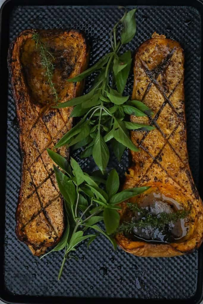 Smoked butternut squash halves on a tray with fresh herbs