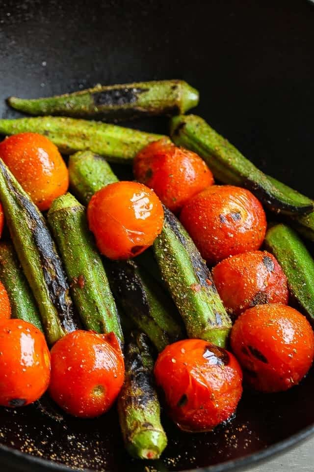 okra and tomatoes cooking in skillet