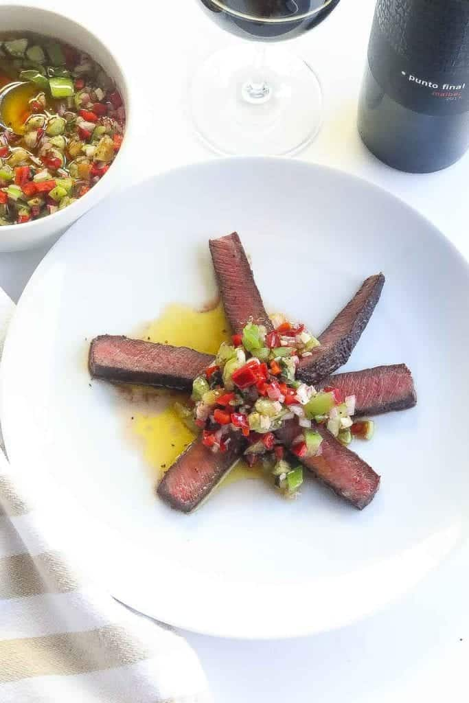 sliced flat iron steak topped with basil tomatillo sauce