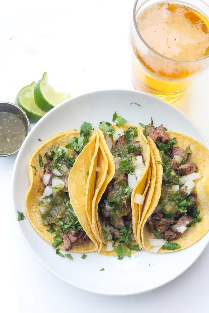 three street tacos on a white plate