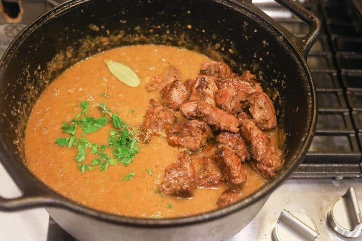 beef and herbs cooking in pot with soup