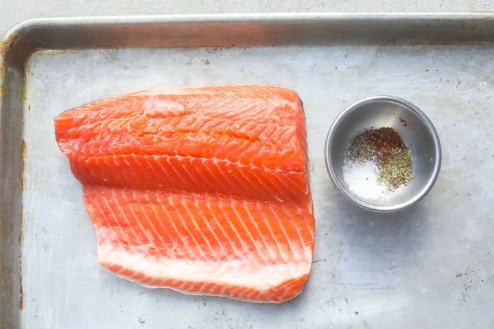raw trout with spice seasonings on a tray