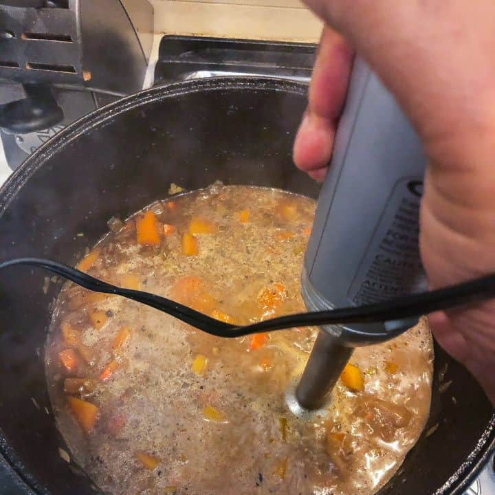 hand blender being used to puree soup ingredients