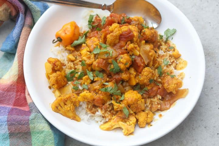 yellow cauliflower florets over rice topped with curry sauce
