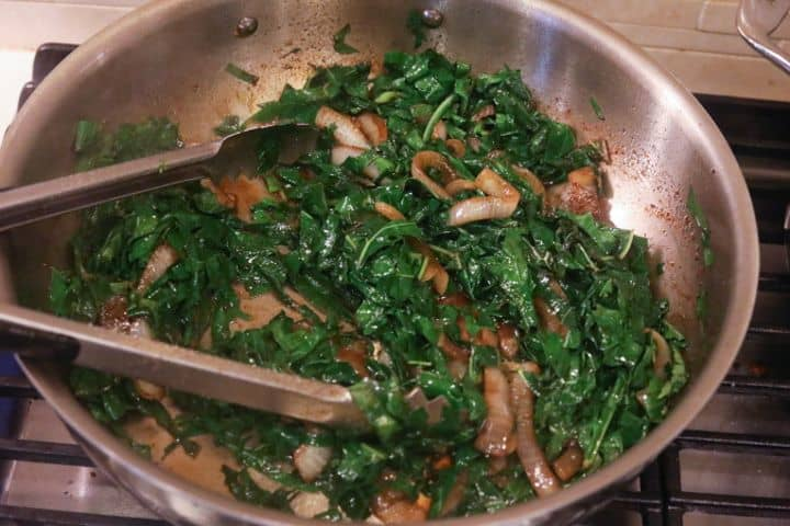 collard greens with onions sauteing in pan