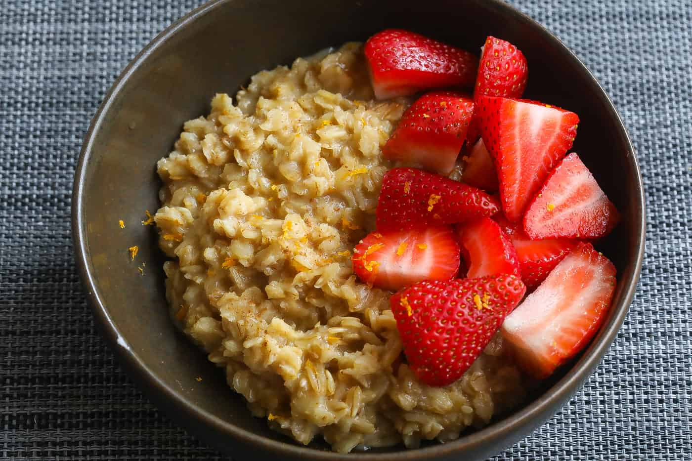oatmeal topped with strawberries in brown bowl