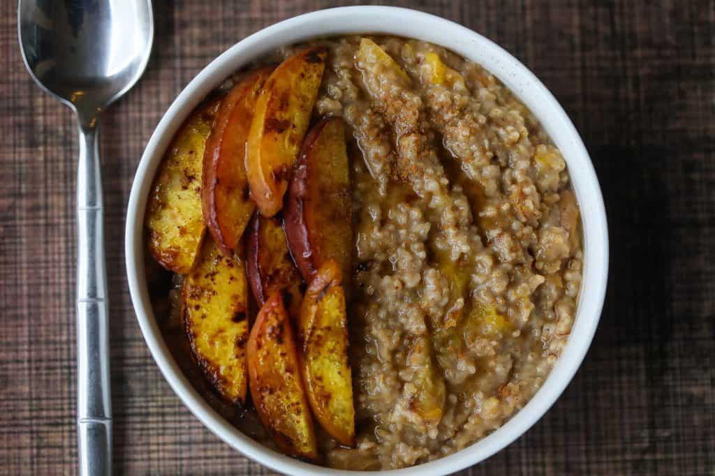 Oatmeal topped with peaches in a white bowl