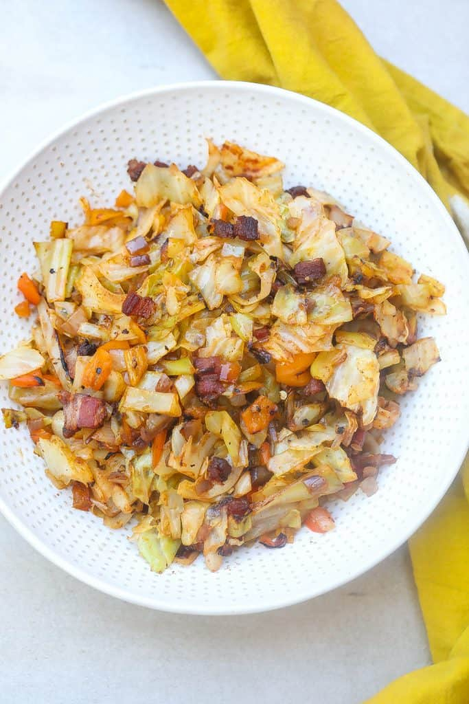 Fried cabbage and bacon on a white plate