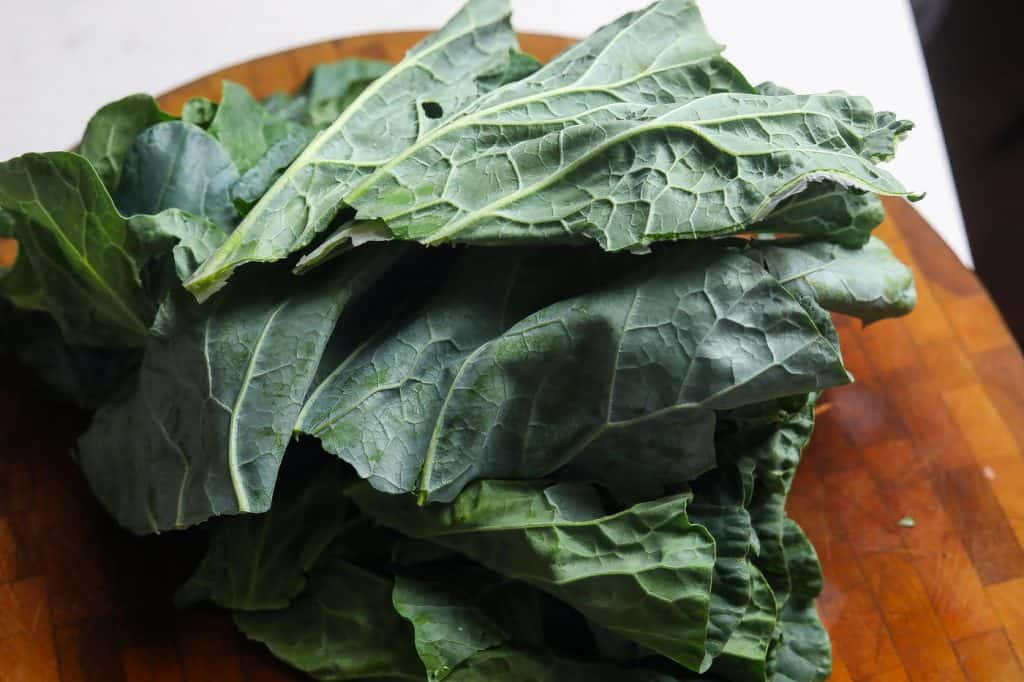 collard leaves stacked on cutting board