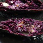 purple sweet potato halves on a black plate