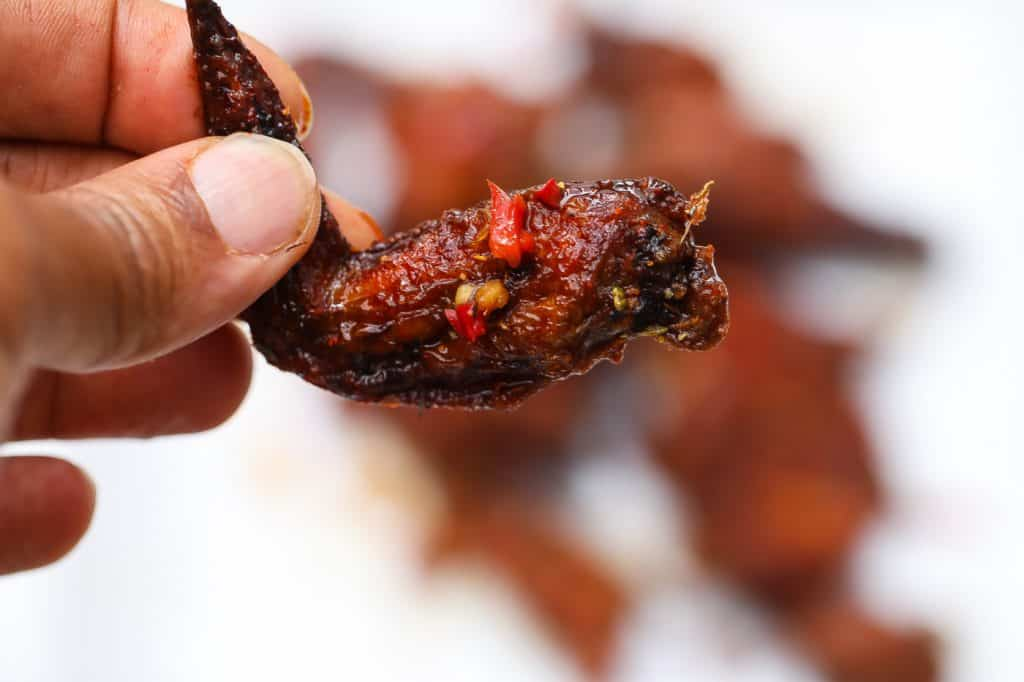 chicken wing held in the air with fingers