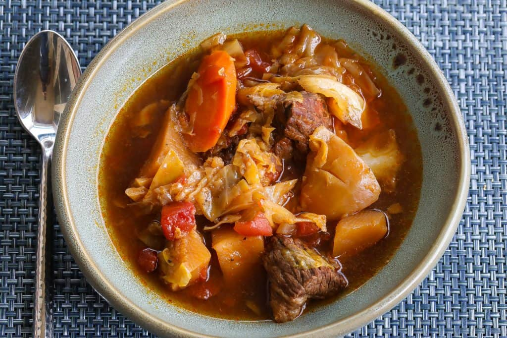 beef and cabbage soup in a large green bowl