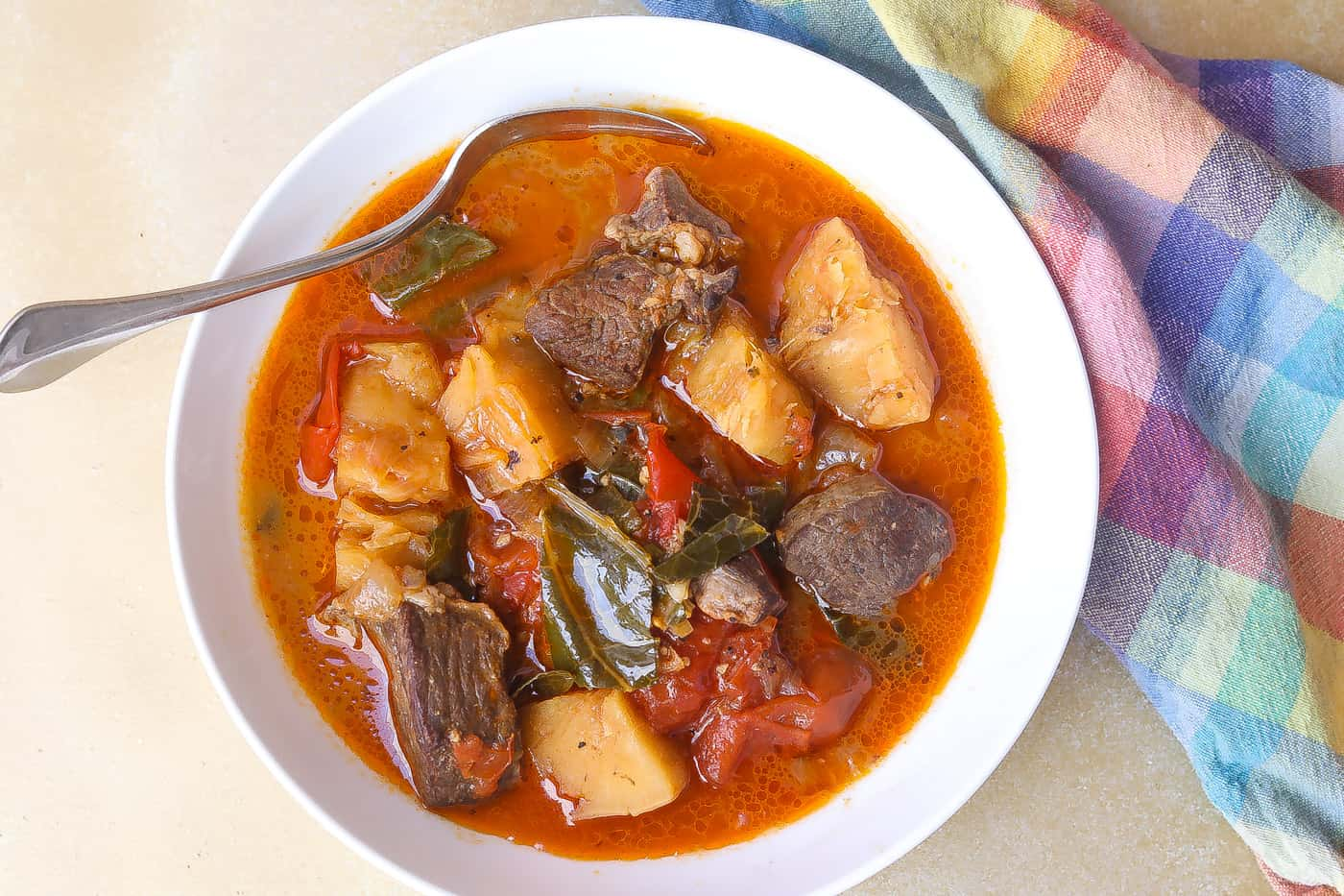 beef soup and vegetables in a white bowl