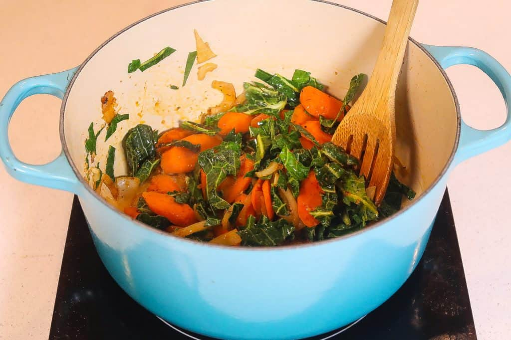 collards and carrots cooking in a blue pot