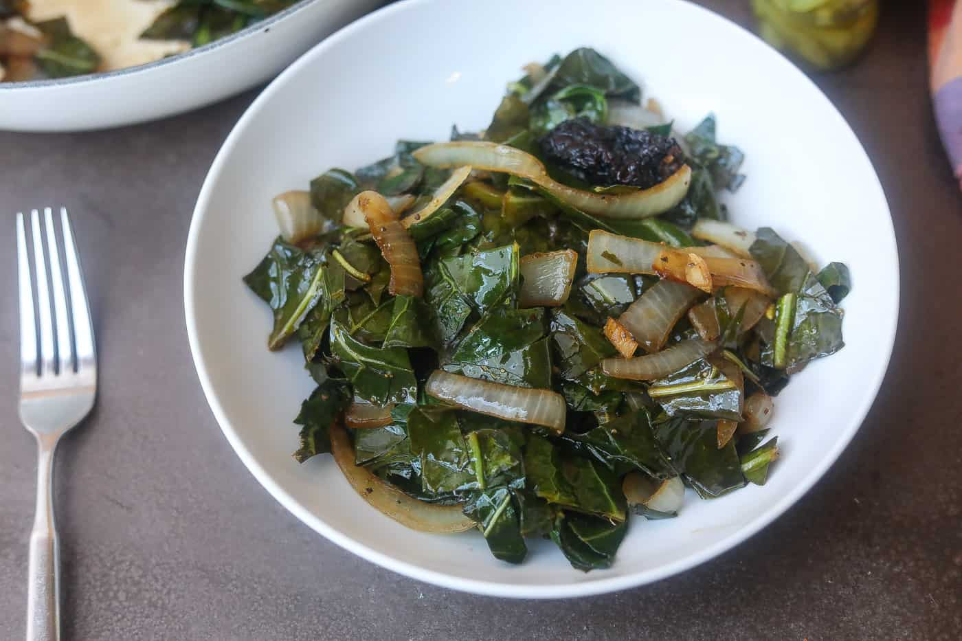 collard greens and onions in white bowl