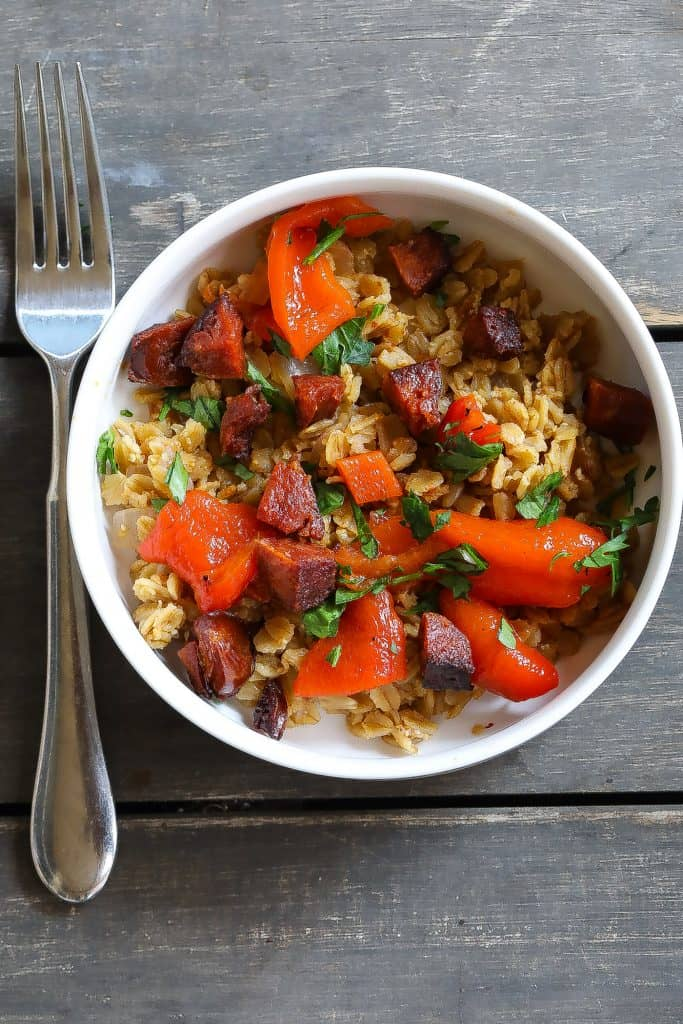 oatmeal with sausage and red peppers in a white bowl