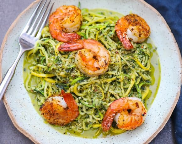zoodles with pesto topped with shrimp on green plate