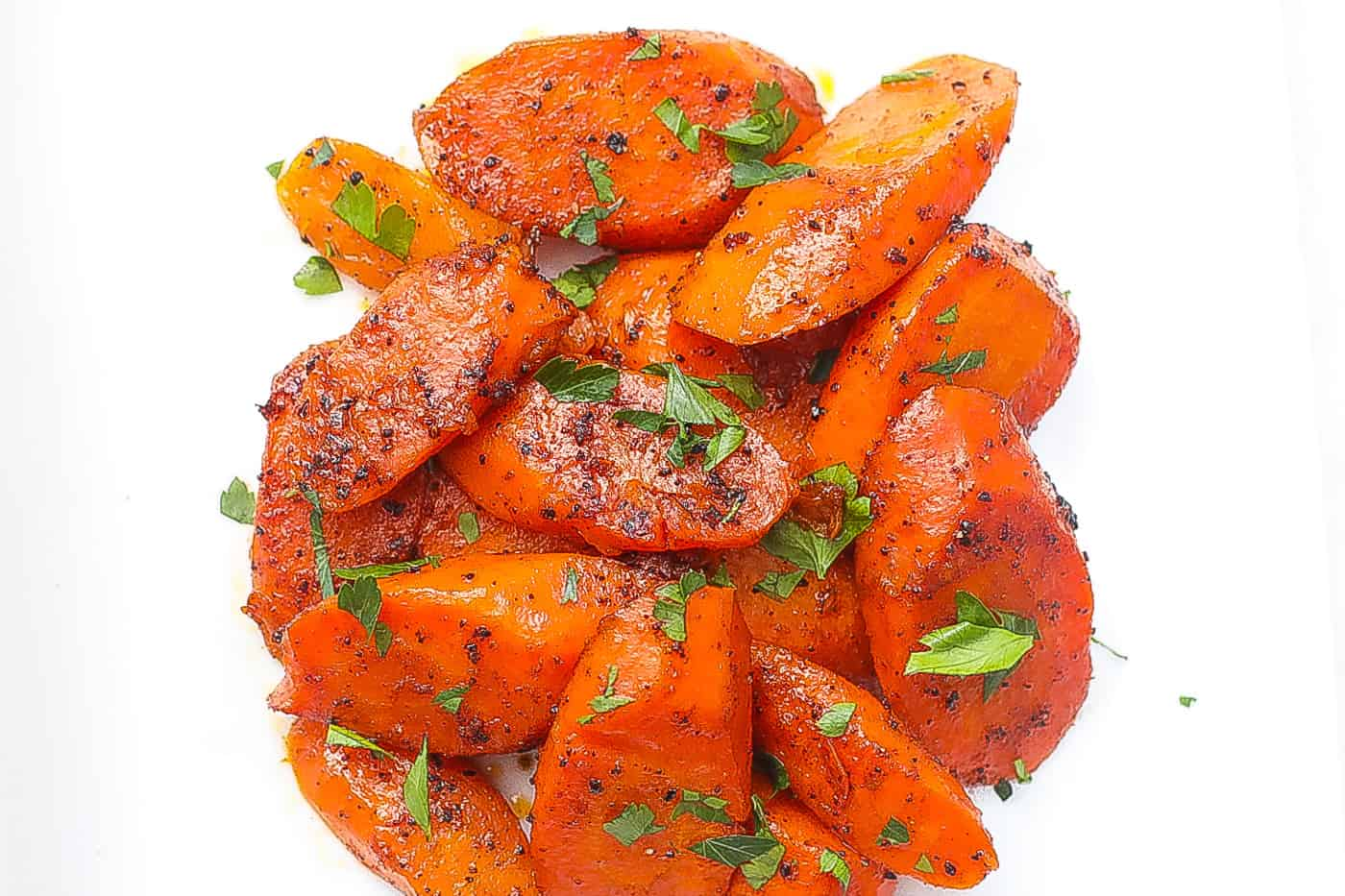 sliced carrots topped with parlsey on a white plate