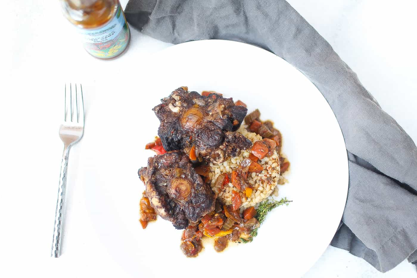 jamaica oxtail on white plate with brown rice