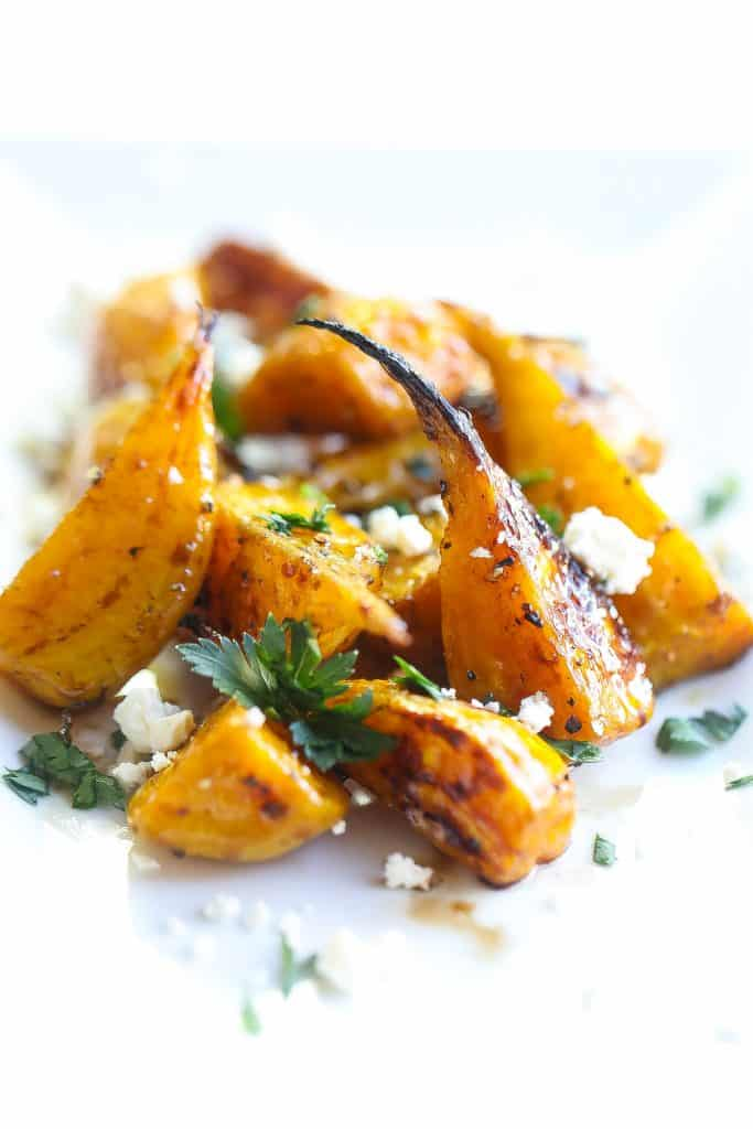 golden beets on a white plate topped with feta and parsley