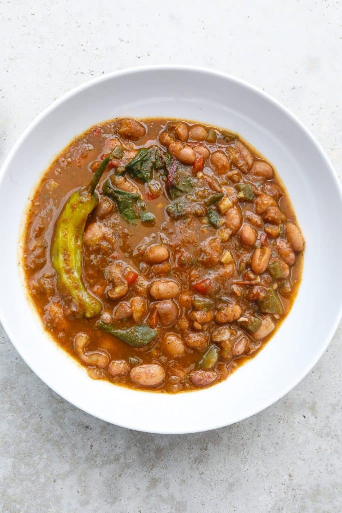 cranberry beans in a white bowl with greens and a pepper
