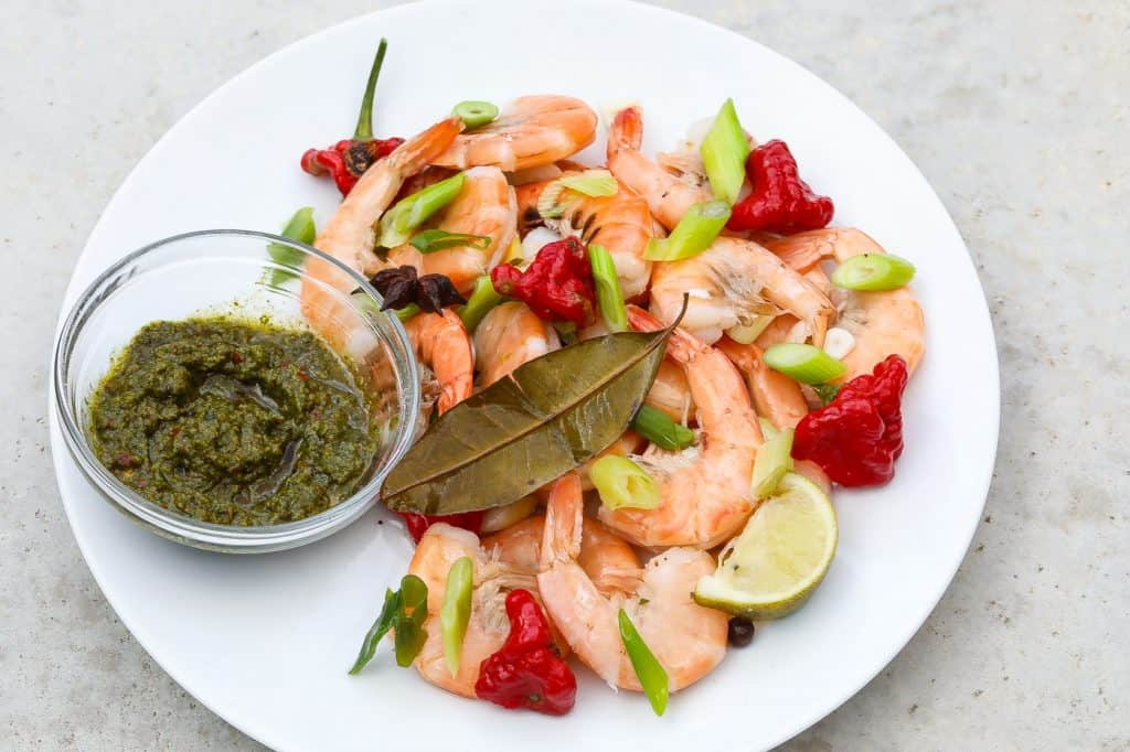 spicy peel and eat shrimp on white plate with red peppers